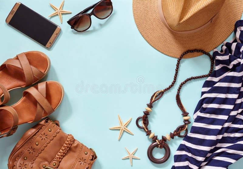 Sommarhavsbakgrund och kvinna` s sätter på land tillbehör på en tur till havet: sugrörhatt, armband, lädersandaler, exponeringsgl royaltyfria foton