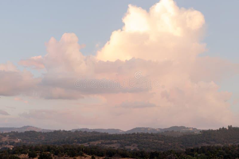 Sommarhimmel som fylls med solnedgång färgade stackmolnmoln över berg, kullar och skoglandskap royaltyfri bild