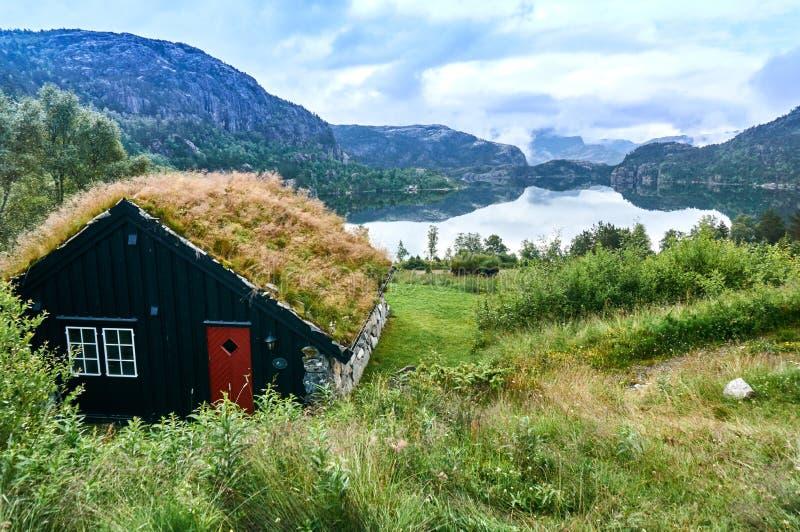 Sommarhus på sjön i de norska bergen arkivbild