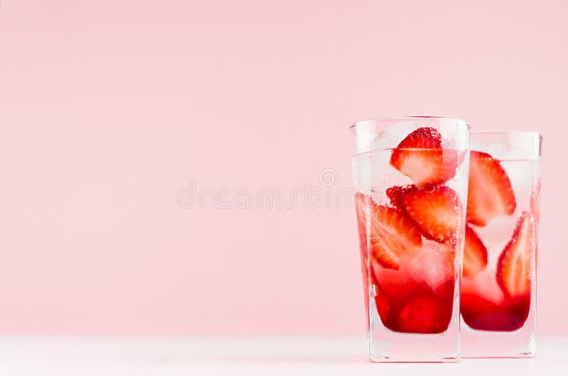 Sommarjordgubbelemonad med iskuben, skivor bär, sodavatten på den eleganta pastellfärgade rosa väggen och den vita trätabellen, k royaltyfri fotografi