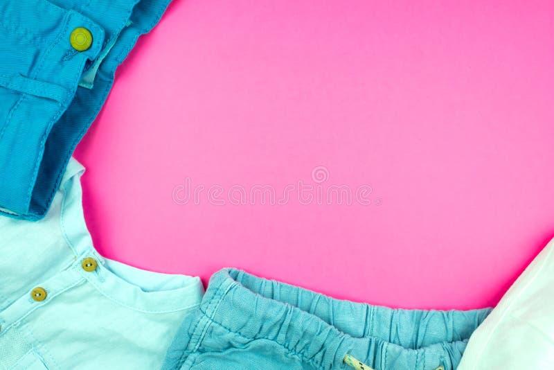 Sommarkläder, kortslutningar, flåsanden och t-skjortor på en rosa bakgrund arkivfoton