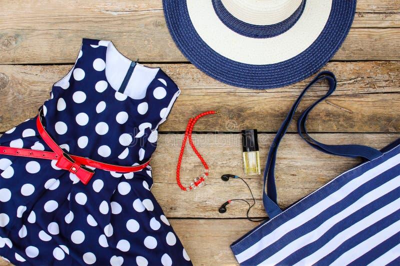 Sommarkläder och tillbehör: klä, börs, hatten, hörlurar, doft, handväskan och pärlor arkivfoto