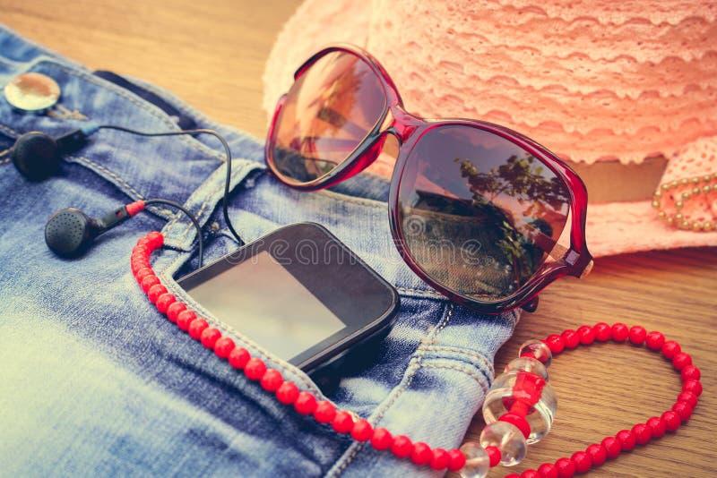 Sommarkvinnors tillbehör: den röda solglasögon, pärlor, grov bomullstvill kortsluter, mobiltelefonen, hörlurar, en solhatt tonad  royaltyfri bild