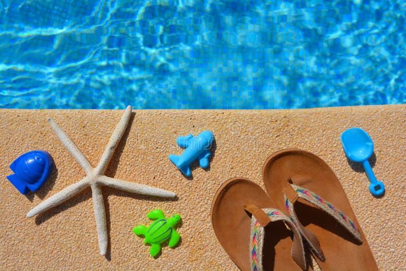 Sommarlägenheten lägger, flipflops, leksaker och sjöstjärnan vid poolsiden, arkivbild