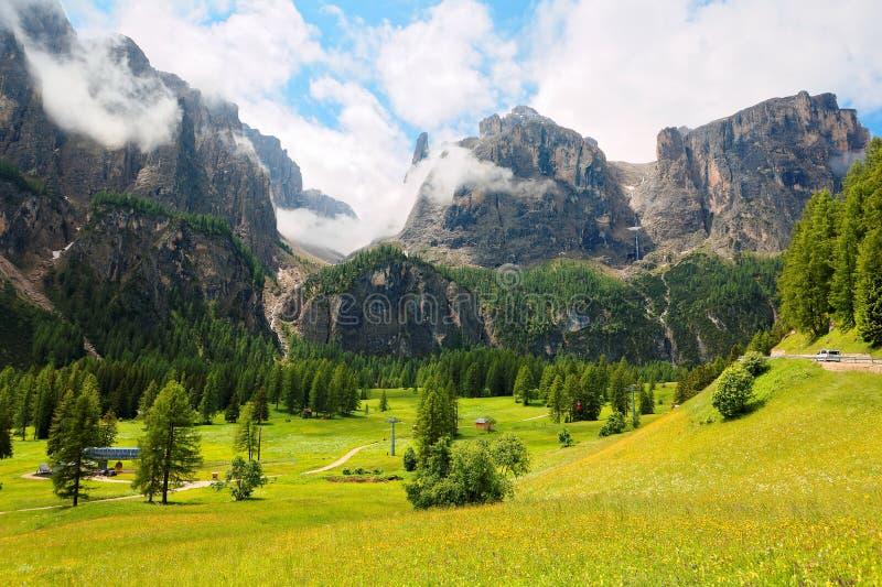 Sommarlandskap av majestätiska Sella berg med vattenfall som dråsar ner steniga klippor in i en härlig grön gräs- dal royaltyfri fotografi