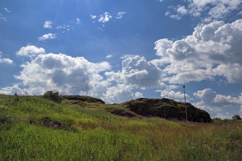 Sommarlandskap Bete med åkergräs på en sluttning mot en bakgrund av blå himmel och vita moln arkivbilder