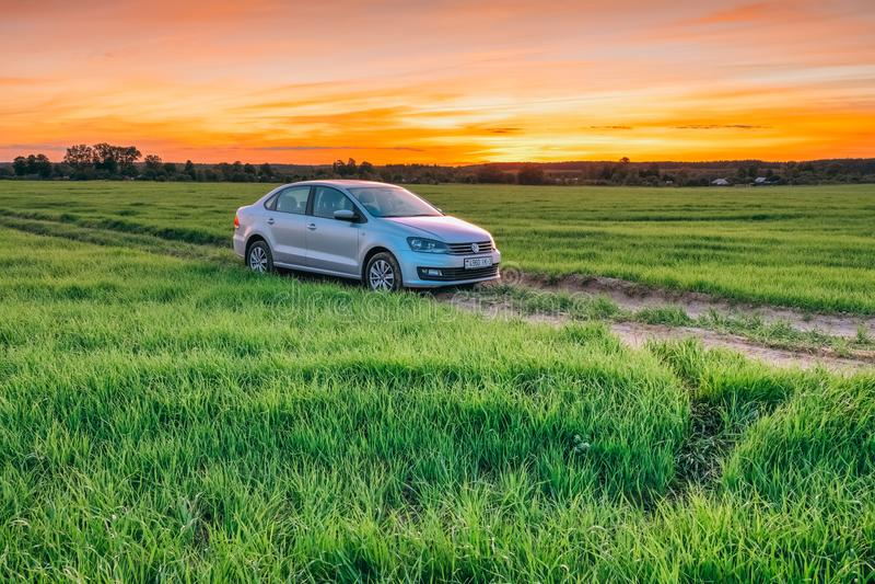 Sommarlandskap på solnedgången med den Volkswagen Polo Vento maskinen in arkivfoto