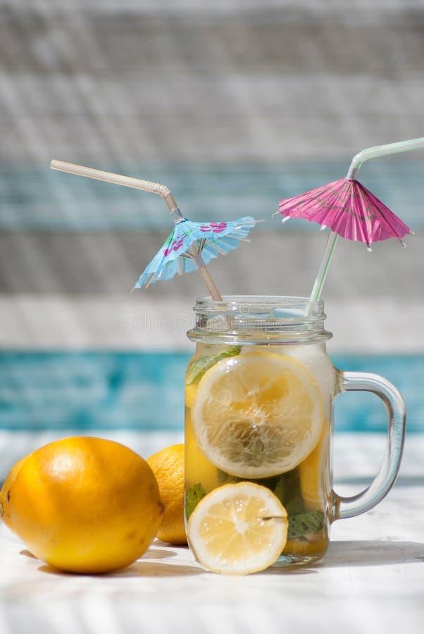 Sommarlemonad med citron-, mintkaramell-, blått- och rosa färgcoctailparaplyer arkivfoton
