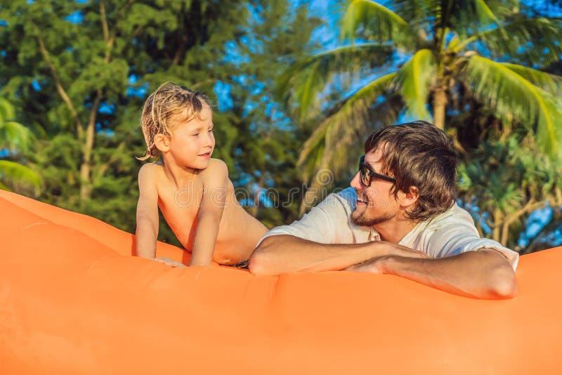 Sommarlivsstilstående av fadern och sonen som sitter på den orange uppblåsbara soffan på stranden av den tropiska ön arkivfoto