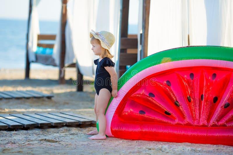 Sommarlivsstilstående av nätt flickasimning som poserar på baksidan på den uppblåsbara vattenmelon i havet, bära som är stilfullt royaltyfri foto