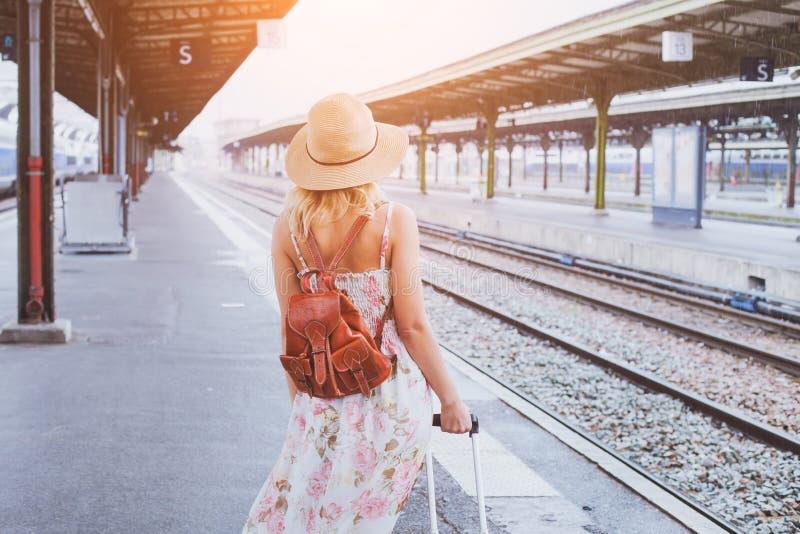 Sommarlopp, kvinna med resväskan som väntar på hennes drev royaltyfria foton