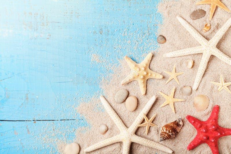 Sommarloppbakgrund från snäckskal, sjöstjärna och sand på blå bästa sikt för tabell royaltyfri fotografi