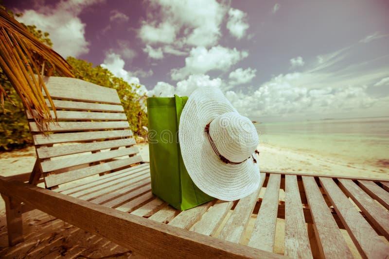 Sommarmode: hatt och påse på vardagsrummet på stranden arkivbild