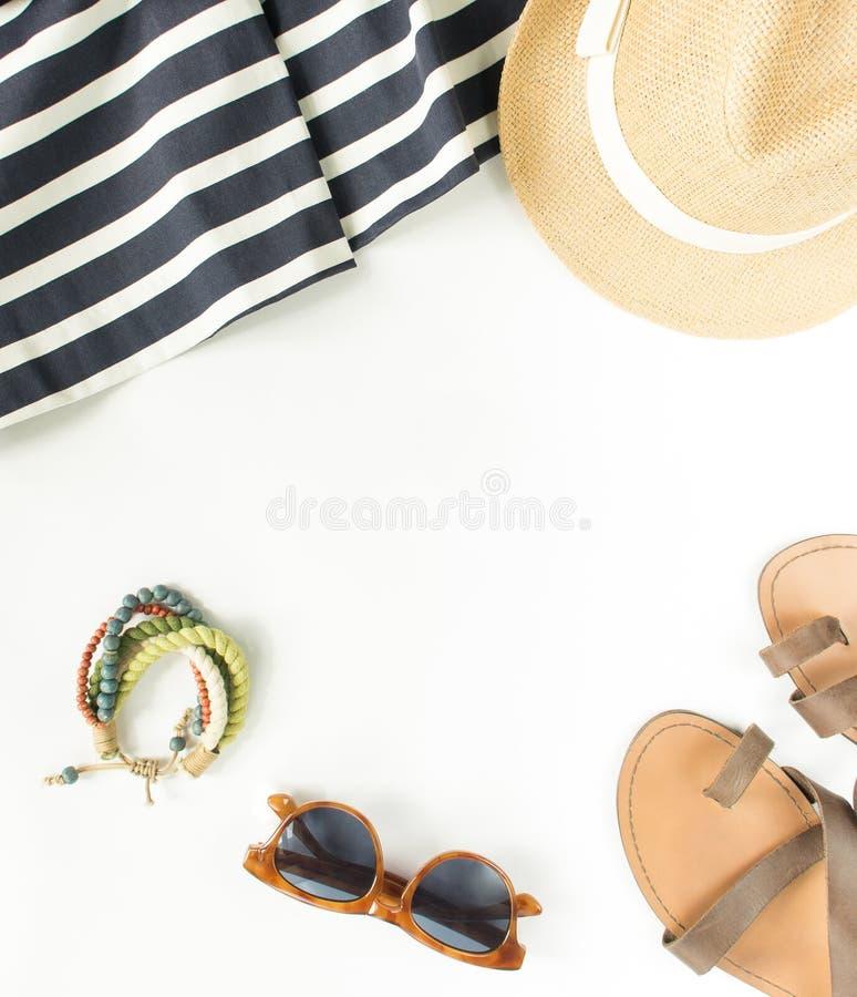 Sommarmode, sommardräkt på vit bakgrund Gjorde randig blått klär, bruna sandaler, retro solglasögon, sugrörhatten, wodarmband f royaltyfri fotografi