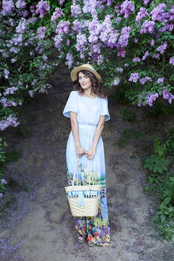 Sommarmodestående av att bedöva kvinnan som går i den blommande lila trädgården Bärande lång tappningklänning Romantisk mood heml royaltyfri fotografi