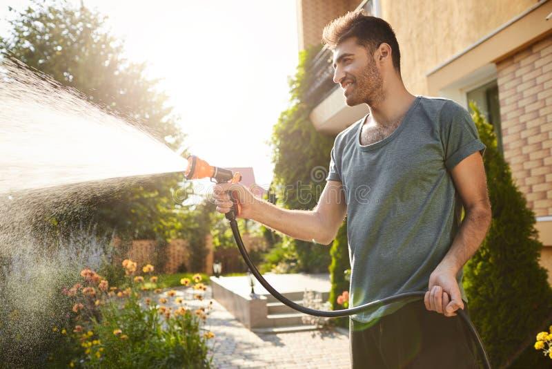Sommarmorgon i bygdhus Stående av den unga attraktiva solbränna-flådde skäggiga mannen i blått t-skjorta le fotografering för bildbyråer