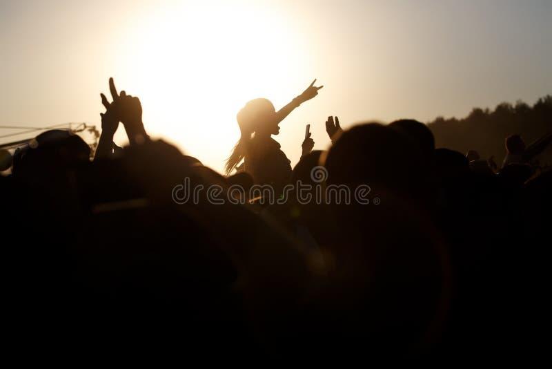 Sommarmusikfestival Folkmassan lyftte händer Flickan får nöje och forsar på smartphonen royaltyfria foton