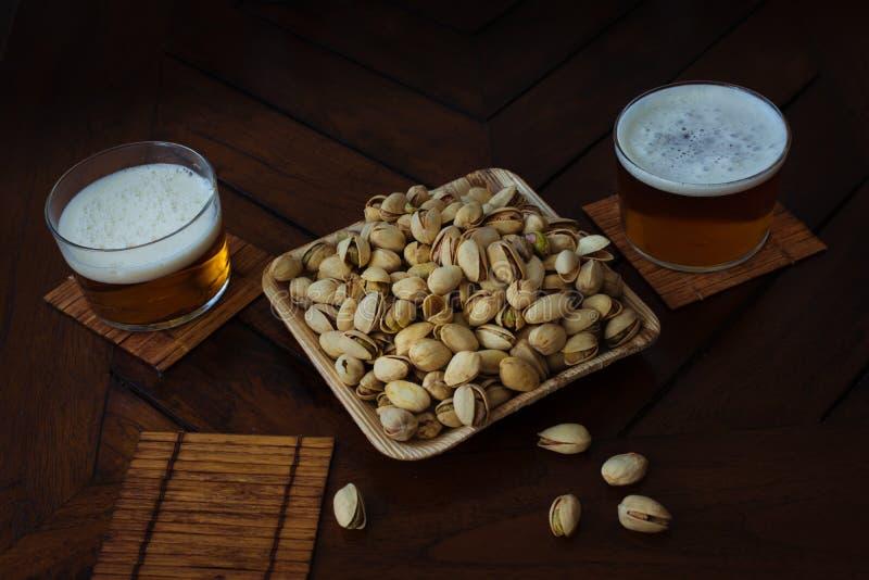 Sommarparti i en bar öl och återanvändbar bunke av pistascher och royaltyfri fotografi