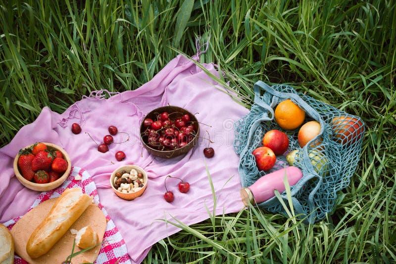 Sommarpicknick på med körsbär i träkokosnötbunkarna, det nya brödet och glasflaskan av fruktsaft royaltyfria bilder
