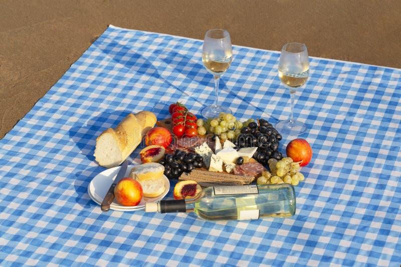 Sommarpicknick p? stranden p? solnedg?ngen Vila med vin p? havet fotografering för bildbyråer