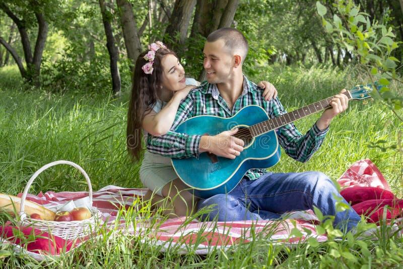 Sommarpicknick, romans grabben spelar hans flickvän på gitarren, leende känslomässigt Lycka royaltyfri foto