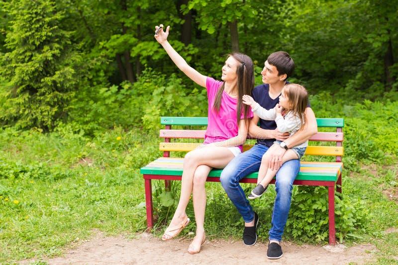Sommarplats av den lyckliga unga familjen som tar selfies med hennes smartphone i parkera arkivfoton