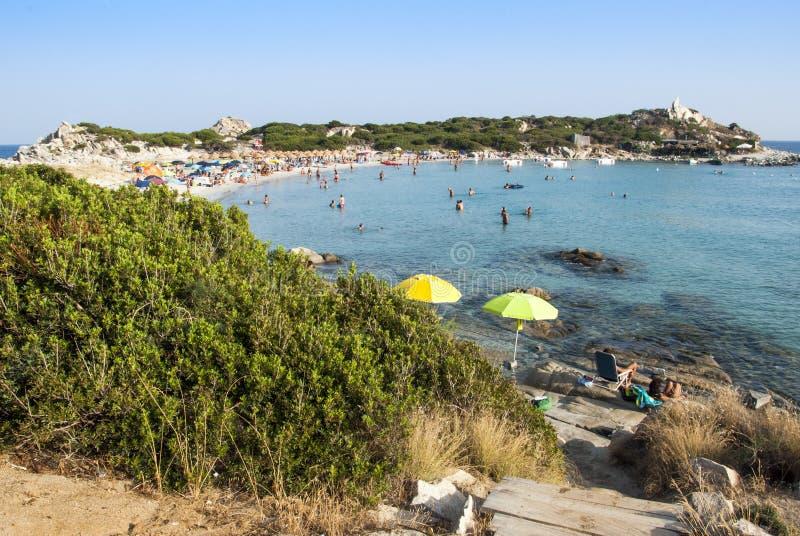 Sommarplats med oidentifierat folk i den vita stranden och blått royaltyfria bilder