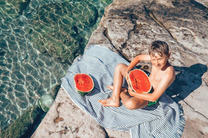 Sommarplesuares: pojke som är klar att äta den stora vattenmelon, når att ha simmat arkivfoton