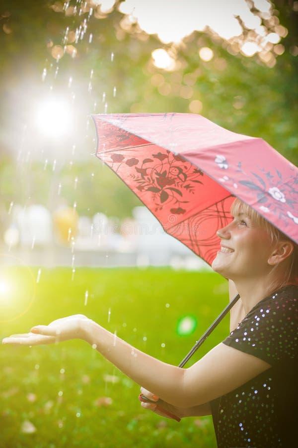 Sommarregn i solnedgången som rymmer en kvinna royaltyfria foton