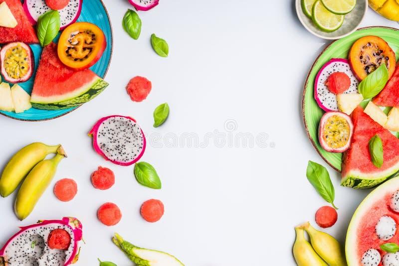 Sommarrengöring och sund livsstilbakgrund med olika färgrika skivade tropiska frukter och bärplattor arkivbild
