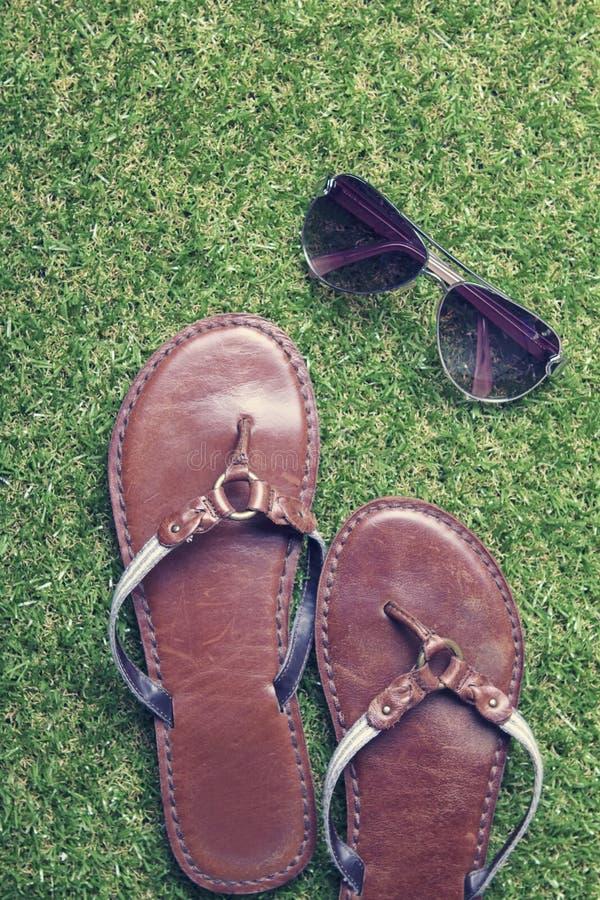 Sommarsandaler och solglasögon på gräs fotografering för bildbyråer
