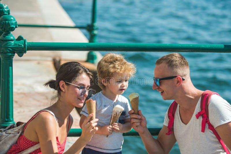 Sommarsemester av den lyckliga familjen Modern och fadern med sonen äter glass på havet Barn med fadern och modern familj arkivbilder