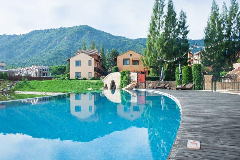 Sommarsemester och feriebegrepp: Träbana eller vandringsled bredvid simbassäng med härlig landskapsikt royaltyfria foton