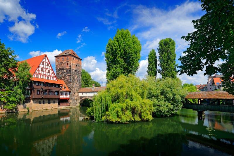 Sommarsikt av den tyska traditionella medeltida korsvirkes- gamla stadarkitekturen och bron över den Pegnitz floden i Nuremberg,  arkivfoton