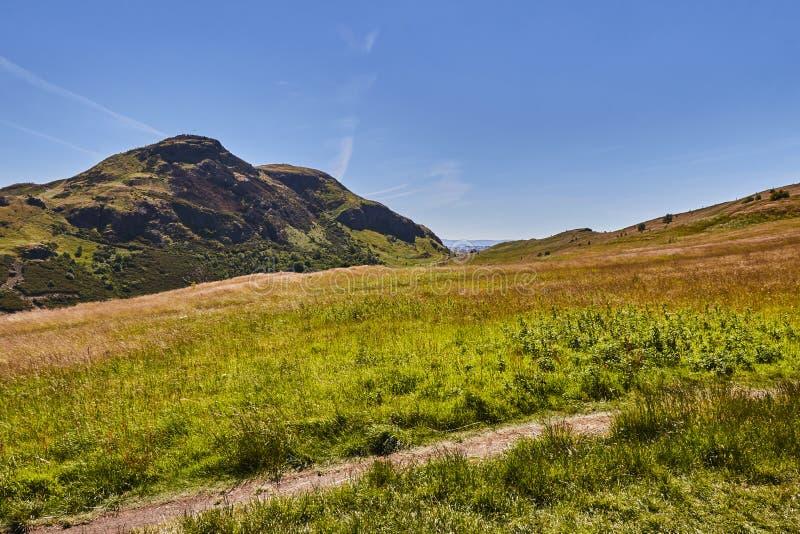 Sommarsikten av Arthur ` s Seat i Holyrood parkerar med härligt grönt gräs och blå himmel i Edinburg, Skottland, Förenade kungari arkivbild