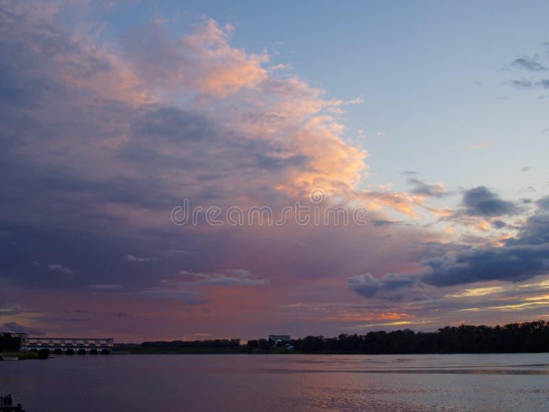 Sommarsolnedgång på floden och den yttre belysningen av den hydroelektriska fördämningen arkivfoton