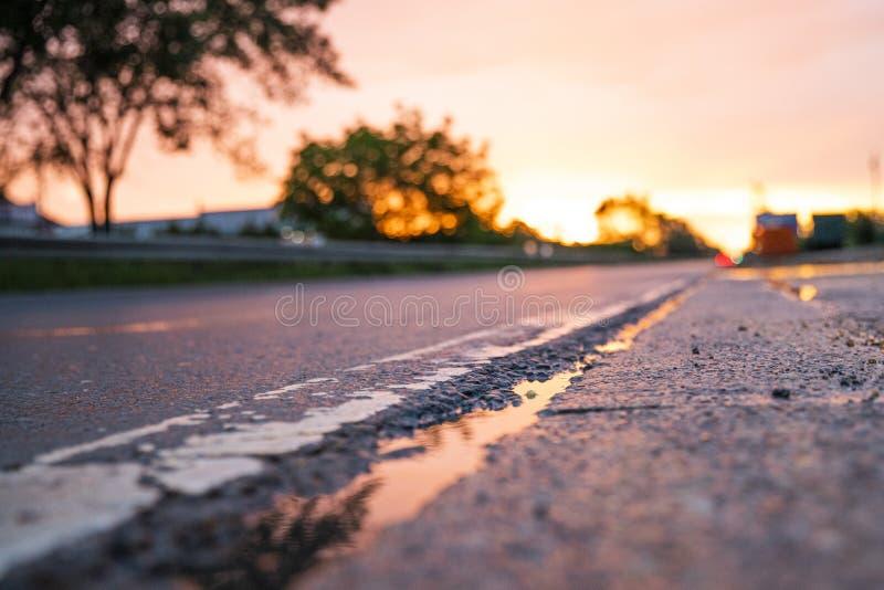 Sommarsolnedgång på väglinjerna med regn arkivbild