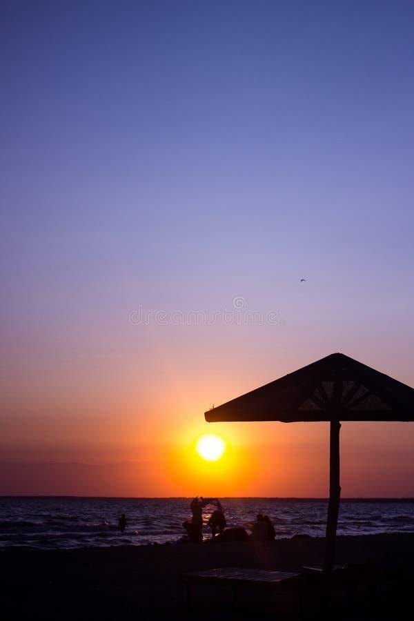 Sommarsolnedgångsol, konturer av strandsvampar, konturer av folk som vilar solnedgång royaltyfri foto