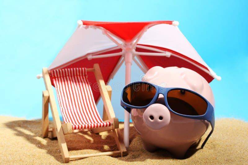 Sommarspargris med solglasögon som står på sand under den röda och vita parasollen bredvid strandstol arkivbild