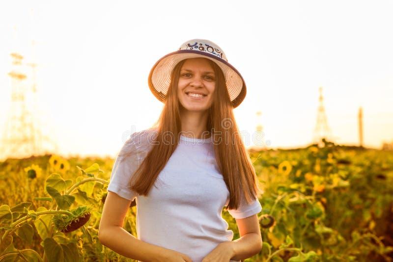Sommarstående av den lyckliga unga kvinnan i hatt med långt hår i solrosfält royaltyfria foton