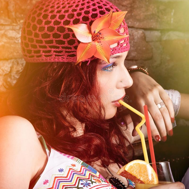 Sommarstående av den unga härliga bohostilkvinnan som dricker fruktsaft med sugrörprofilsikt arkivbild
