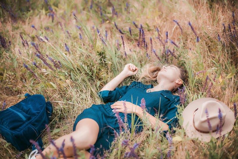 Sommarstående av den unga hipsterkvinnan som ligger i ett gräs på solig dag arkivfoto