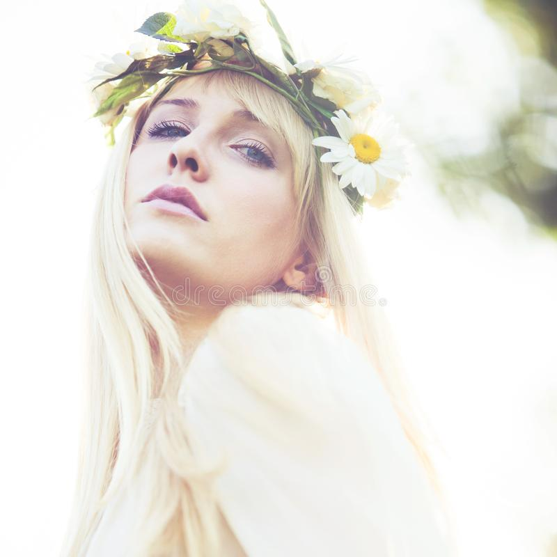 Sommarstående av den unga kvinnan med kransen av blommor i utomhus- skott för hår royaltyfria bilder