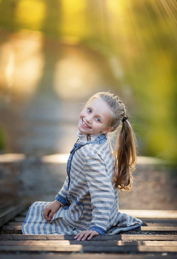 Sommarståenden av den härliga flickan för det lilla leendet som poserar i, parkerar arkivbilder