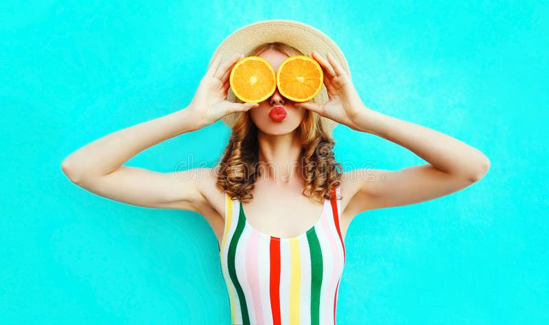Sommarst?endekvinna som rymmer i hennes h?nder tv? skivor av orange frukt som d?ljer hennes ?gon i sugr?rhatt p? f?rgrika bl?tt royaltyfria foton
