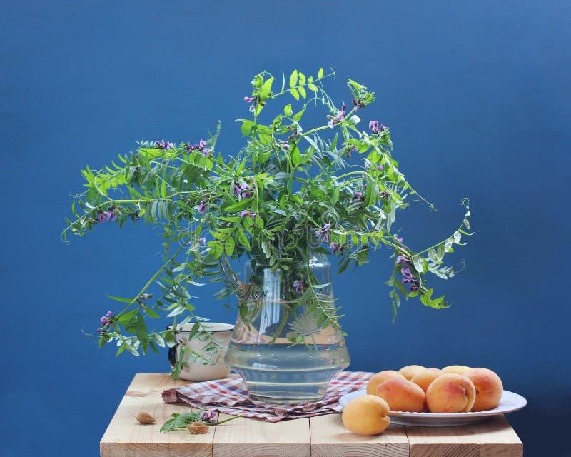 Sommarstilleben med blommor och frukt på en blå bakgrund arkivbilder
