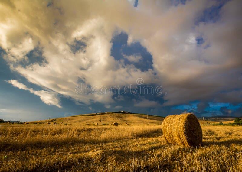 Sommarstormen att närma sig över skördat höfält i Tuscany, Italien royaltyfria foton