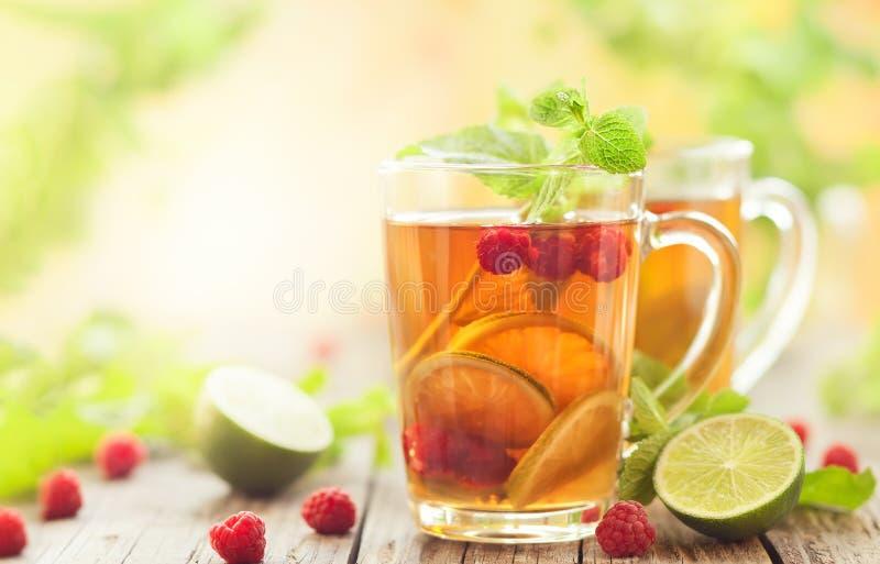 Sommarte med hallon, limefrukt och mintkaramellen p? tr?tabellen royaltyfria foton