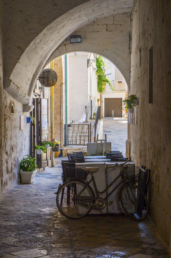 Sommarterrasskafé i en smal valvport av Polignano en sto, Italien royaltyfri bild