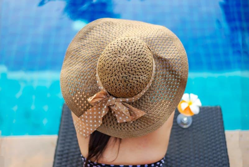 Sommartid och semestrar Kvinnalivsstil som är avslappnande och dricker fruktsaftapelsinen som så är lycklig i lyxig simbassängsun royaltyfri bild